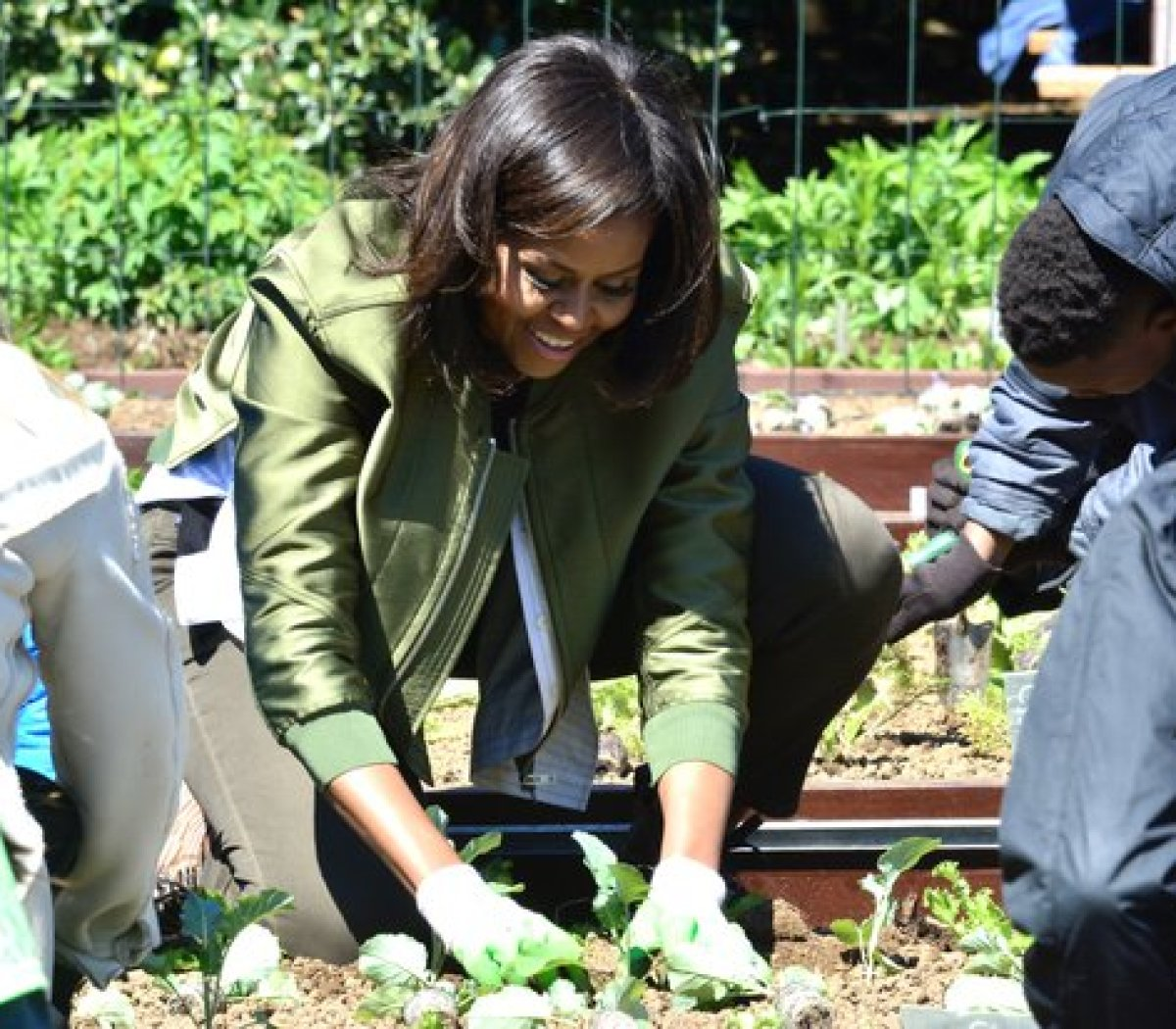 First Lady Michelle Obama gets down to help plant the Kitchen Garden at the White House Tuesday, April 5, 2016. /Photo by Travis Riddick @actor_tr