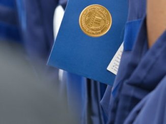 A student holds a program booklet during the 148th Commencement Convocation at Howard University on Saturday, May 7, 2016 in Northwest. /Photo by Patricia Little