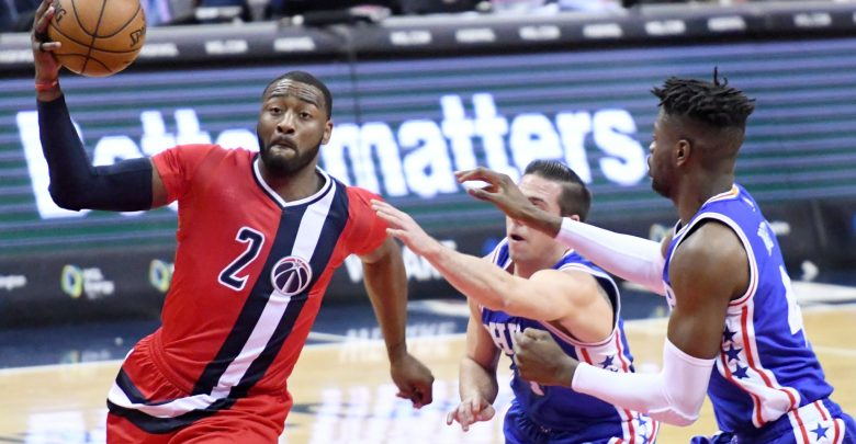 Washington Wizards guard John Wall drives to the basket against two Philadelphia 76ers defenders in the second quarter of the Wizards' 109-93 win at Verizon Center in D.C. on Jan. 14.