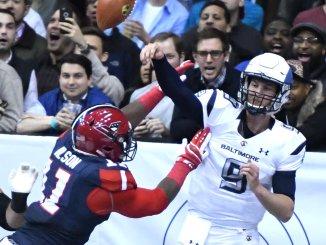 Baltimore Brigade quarterback Shane Carden (9) attempts a pass as Washington Valor defensive lineman Reggie Wilson closes in during the first quarter of the Valor's 51-38 win at Verizon Center in D.C. on April 7. (John E. De Freitas/The Washington Informer)