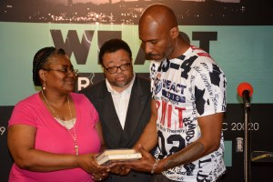Kenneth McClenton (center) and Francine Milton present Kymone Freeman with two of Charnice Milton's favorite books for the Charnice Milton Community Bookstore housed in the We Act Radio building in southeast D.C. on May 17. (Roy Lewis/The Washington Informer)