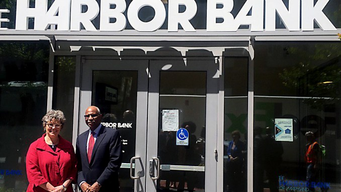 Harbor Bank CEO Joseph Haskins Jr. stands outside his bank with Annie Donovan of the federal Community Development Financial Institutions Fund. (Courtesy photo)