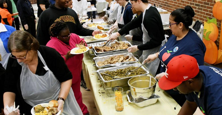 Volunteers with Children of Mine Youth Center, Inc., Our Lady of Perpetual Help Catholic Church and Martha's Table partner on Nov. 18 to serve Thanksgiving dinner at the Panorama Room in southeast D.C. (Roy Lewis/The Washington Informer)