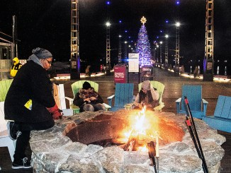 "Bobbi Lancaster, fire pit attendant at The Wharf in southwest D.C., keeps things ""fired up"" during the new family-friendly center now featuring holiday activities. (Shevry Lassiter/The Washington Informer)"