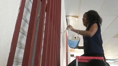 Raisa Dorsaindville, 20, paints a wall inside La Hermosa Church in downtown Arecibo, Puerto Rico. (Tatyana Hopkins/NNPA)