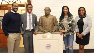 From left: Howard University School of Law professor Justin Hansford and law students Elijah Porter, Hayley Tharpe and Ky'eisha Penn pose with a statue of Thurgood Marshall, an alumnus of the law school. (Brigette White/The Washington Informer)