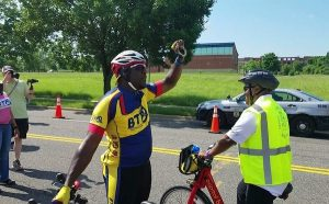 Ray Ferguson raises his hand to give brief instructions to bicyclists, including Prince George's County Executive Rushern L. Baker III (right), before a short ride from the Wayne K. Curry Administration Building to the Largo Town Center Metro station on June 1 as the county launched its Capital Bikeshare operation. (William J. Ford/The Washington Informer)