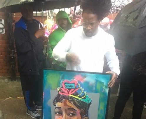 A mourner holds a painting of Makiyah Wilson at a recent candlelight vigil at Clay Terrace in Northeast. (Sam P.K. Collins/The Washington Informer)
