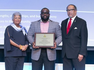 Lester A. Booker Jr. (center), the Corporate Giving Communications Lead for General Motors, accepts the 2018 National Meritorious Leadership Award on behalf of the global automaker at the NNPA's annual convention in Norfolk, Va. NNPA Chairman Dorothy Leavell (left) and NNPA President and CEO Benjamin F. Chavis Jr. present the award. (Mark Mahoney/NNPA)