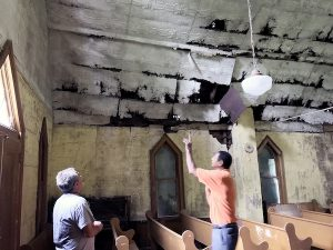 Jay Meredith (left) and Tyrone Pinder examine the interior of historic Bazzel United Methodist Church in Bucktown, Md. Pinder's grandfather assisted in the church's construction in 1911. (Courtesy of John Muller)
