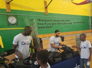 Capital City Go-Go head coach Jarell Christian (right) and general manager Pops Mensah-Bonsu distribute backpacks to youth after a basketball clinic at Charles Hart Middle School in southeast D.C. on Aug. 8. (William J. Ford/The Washington Informer)