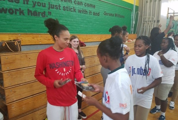 Washington Mystics point guard Kristi Toliver hands a mouthguard to a youth during a Jr. WNBA basketball clinic at Charles Hart Middle School in southeast D.C. on Sept. 11. (William J. Ford/The Washington Informer)