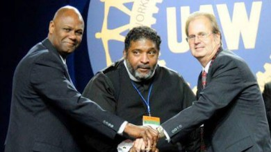 UAW Secretary-Treasurer Ray Curry, Rev. William Barber II, and UAW President Gary Jones stand in solidarity following Rev. Barber's speech on equality.