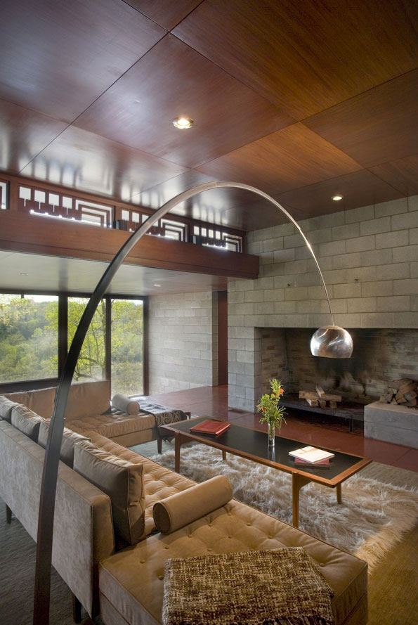 """An iconic Arco floor lamp soars over the central living space toward a stone fireplace. Wright often described fireplaces as """"the heart and soul of a house."""""""
