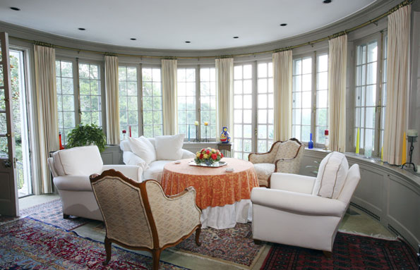 Comfortable armchairs pulled up to a round table provide a space for conversation and a casual meal in the window-enclosed bay at the back of the house.