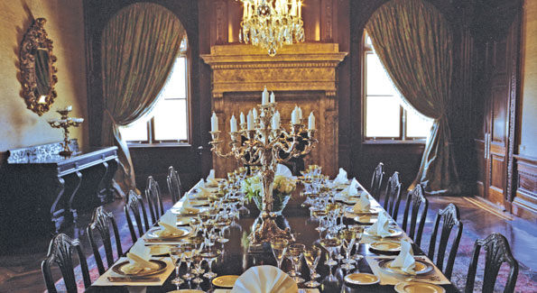 The dining room features a magnificent bronze and silver Balthazar clock, three silver and crystal chandeliers, and two 18th century silver-arm candelabras atop an original Hepplewhite dining table.