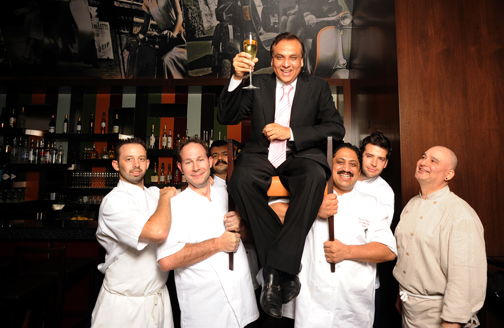 "Raise a glass (and a chair)Raise a glass (and a chair) to Ashok Bajaj (seated), who ""feeds the in-crowd"" at seven of Washington's top restaurants. Left to right: executive chefs Adam Longworth (701 Restaurant), Tony Conte (The Oval Room), Nilesh Singhvi (The Bombay Club), Vikram Sunderam (Rasika) Nicholas Stefanelli (Bibiana), and Alex McWilliams (Ardeo and Bardeo) (Photo by James R. Brantley)."