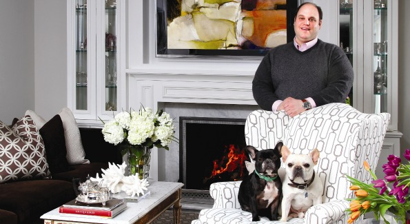 "Jeff Akseizer and his French Bulldogs LuLu and Louie love to entertain in the living room of his renovated McLean, Va. home. He paired a hickory chair wingback with a Bolier & Co. sofa in rich warm colors and added a David Hicks patterned Stark rug, antique coffee table with 14-kt. gold trim and Carrera marble top, and rare coral for color and contrast. The built-ins around the fireplace, which is his favorite ""accessory"" in the house, are from his own ADG Millwork Shop in Boswell, Penn. Additional decor by Jamie Brown of Akseizer Design Group."