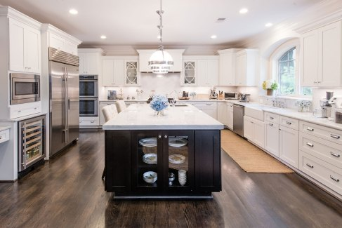 The spacious kitchen features marble counters, double ovens, two dishwashers, pendant lights from Restoration Hardware and white Dura Supreme cabinetry.