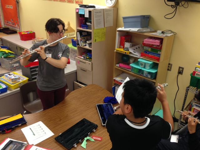 WSC member Naomi plays flute with a young student.
