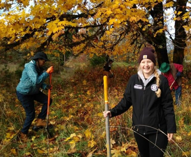 WSC member Kassandra posing in a wooded area in the fall with volunteers.