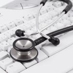 Ein Stethoskop liegt auf einer Computer-Tastatur