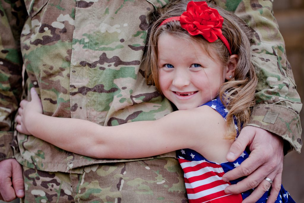 A smiling young girl hugging her soldier father