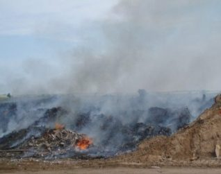 Image of a burning landfill which would not achieve Landfill Directive Compliance.