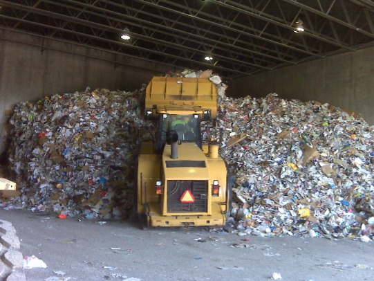 Image shows a front loader vehicle in a waste transfer station.