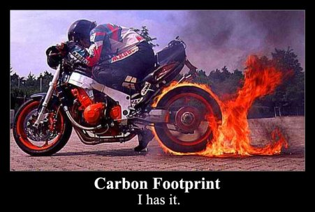Image shows burning carbon onto a road! It illustrates the concept of a carbon footprint.