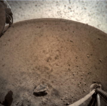 NASA's InSight spacecraft flipped open the lens cover on its Instrument Context Camera (ICC) on Nov. 30, 2018, and captured this view of Mars. Located below the deck of the InSight lander, the ICC has a fisheye view, creating a curved horizon. Some clumps of dust are still visible on the camera's lens. One of the spacecraft's footpads can be seen in the lower right corner. The seismometer's tether box is in the upper left corner. Courtesy NASA/JPL-Caltech