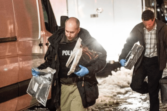 Police officers carry bagged evidence out of a house in Kingston that had been raided on Thursday evening. (Courtesy Lars Hagberg/Canadian Press)