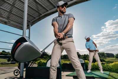 swinging golf club while wearing wrist watch