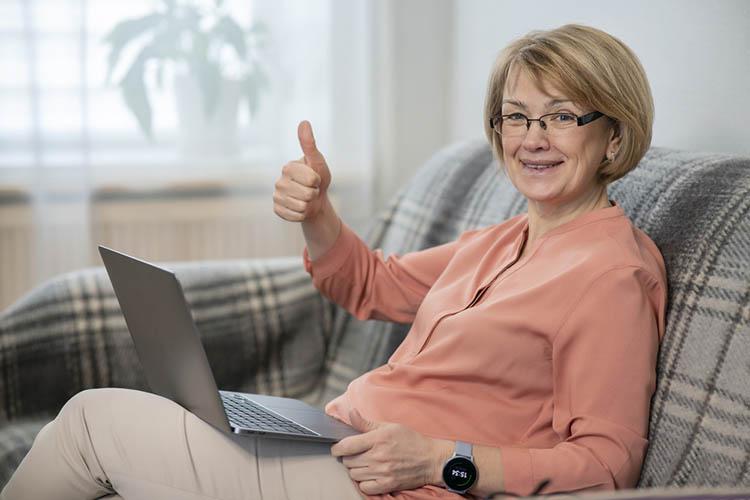 Senior using laptop and smartwatch