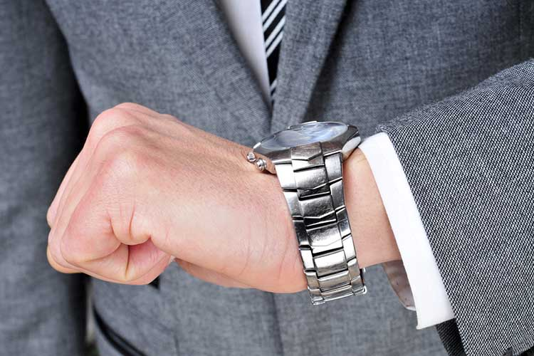 a man wearing a suit looking at his watch