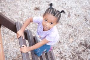 Girl climbing a wooden ladder on a playground