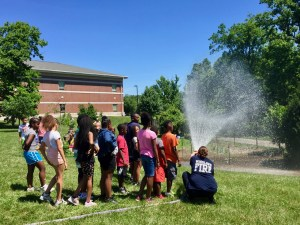 Katie Thielmeyer from Woodlawn Fire Department helping children use fire hose to water Woodlawn garden