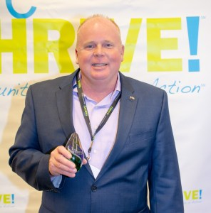 Bryan holding Champion award standing in front of WeTHRIVE! banner