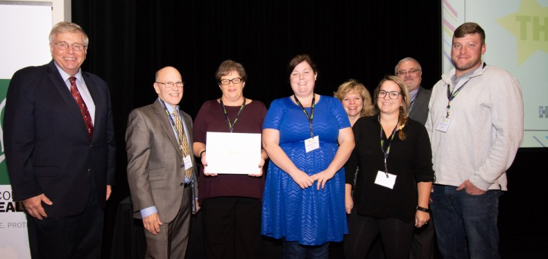 picture of health commissioner and board of health members presenting WeTHRIVE! award to the Reading We Thrive team, standing