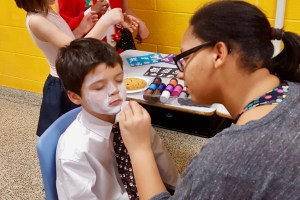 Female student painting child's face at event.