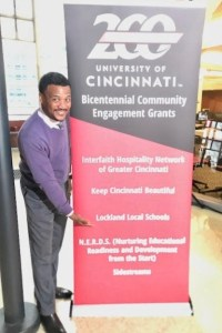 Principal Comer standing next to sign that lists grant recipients for UC Bicentennial Community Engagement Grants.
