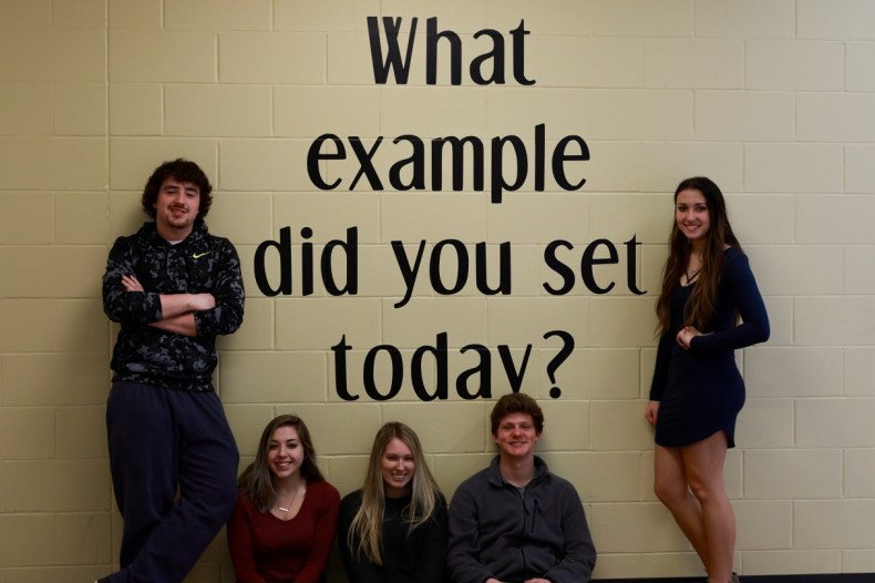 5 high school students standing and sitting around sign that says what example did you set today
