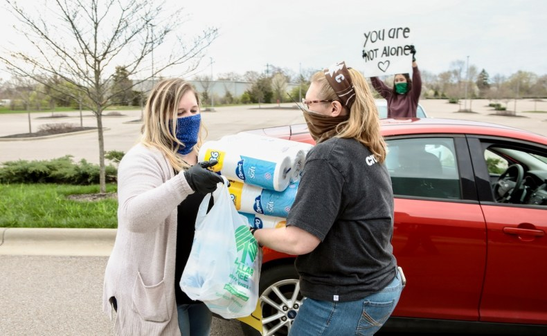 two women next to car with bag of supplies and person in background holding sign that says you are not alone