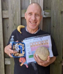 adult male holding fitness challenge tracking form, water bottle, fruits and vegetables