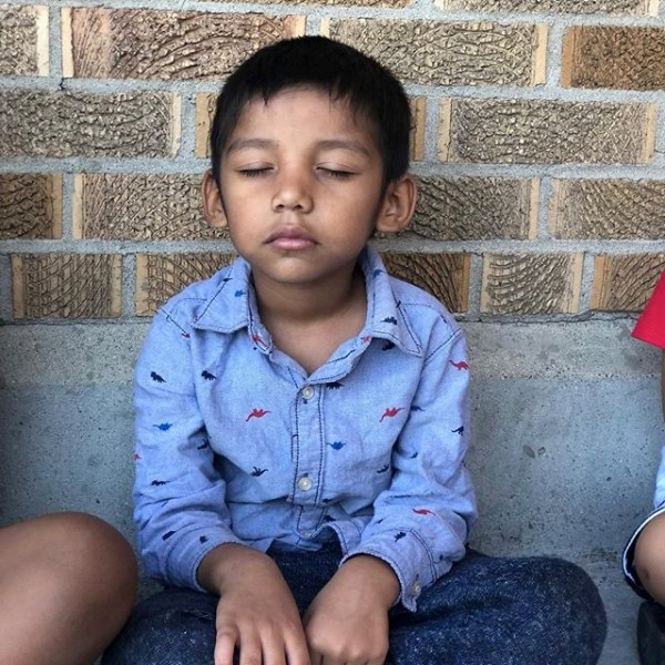 young boy sitting cross legged against brick wall with eyes closed relax meditation