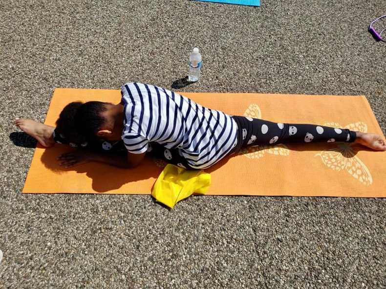 ballet student doing splits and stretching on yoga mat outside