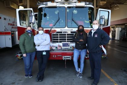 two firefighters and two students standing in front of fire truck