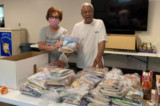 two adults behind table filled with bags of books