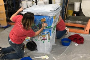 trash bin being painted by two people