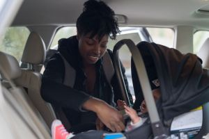 woman putting infant into car seat